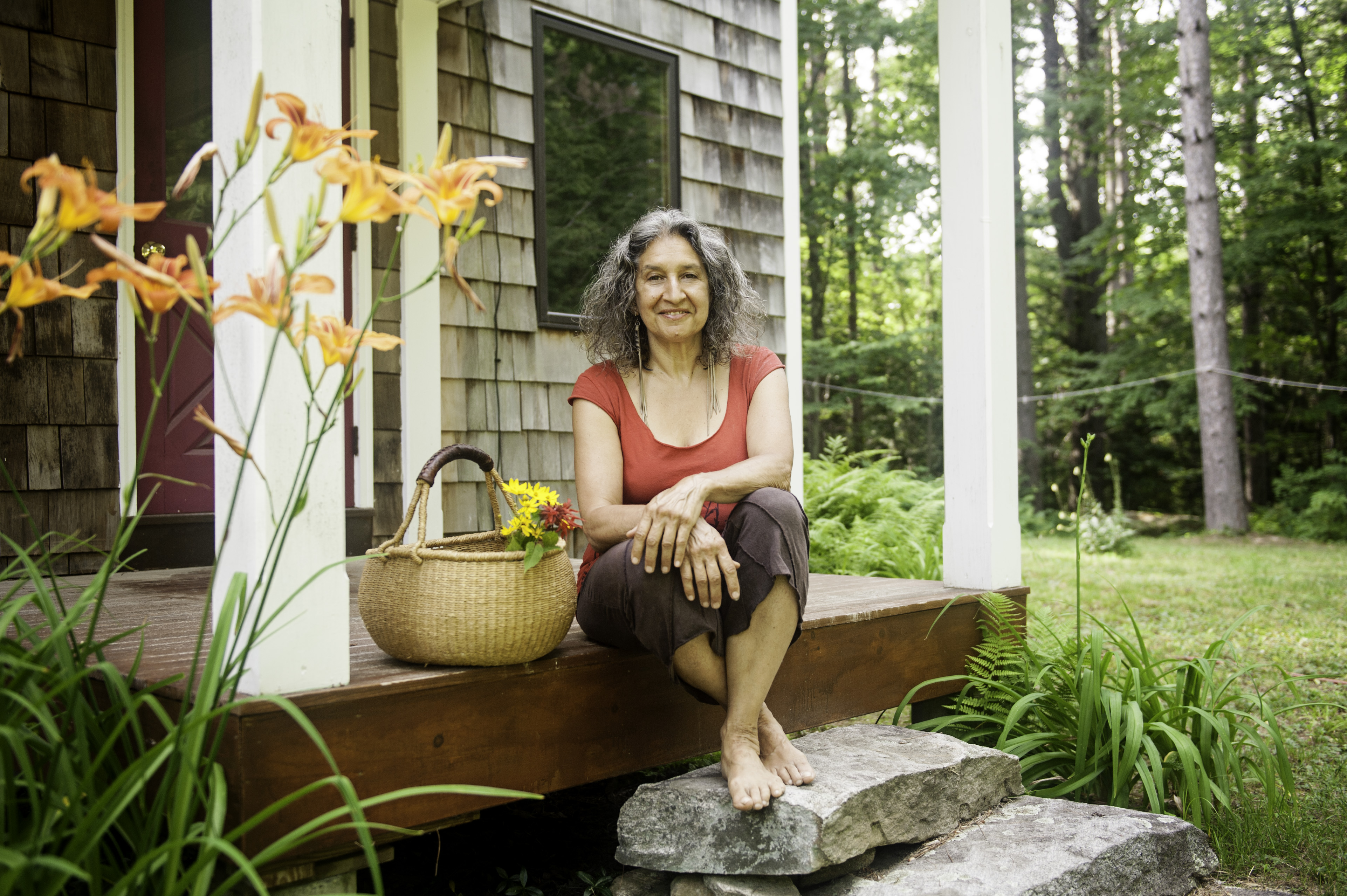 Leslie siting on the back porch of her natural passive solar home in summer