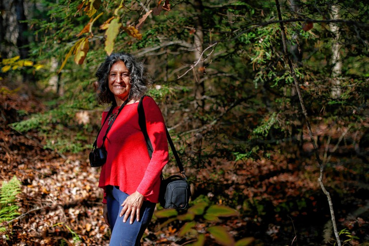 Photographer Leslie Cerier poses for a portrait Nov. 4 in the woods near her Shutesbury home.