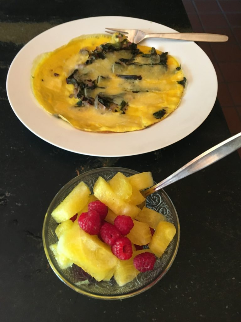 Organic cheese and vegetable omelet with fresh organic fruit salad